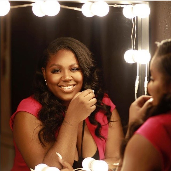 Tanya Johnson is sown smiling at the camera while staring in a mirror with light globes surrounding it.