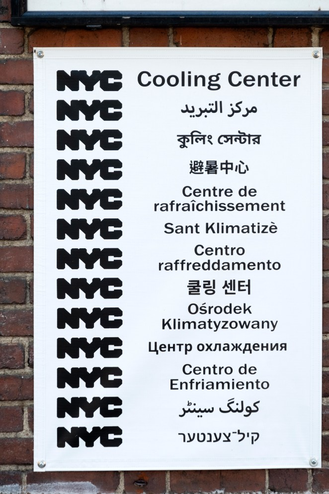 "A white sign on brick that reads ""Cooling Center"" in 13 languages"