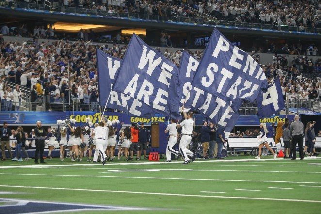 """Four men run on grass in a packed stadium as they hold giant flags that read """"We Are Penn State"""""""