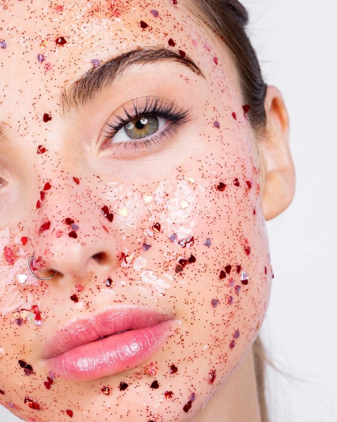 The jelly face mask applied on a model showing a translucent base with red glittery hearts