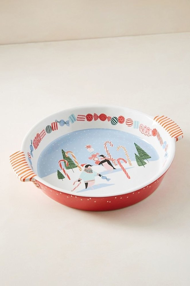 a red pie dish with a white inside showing a wintry scene