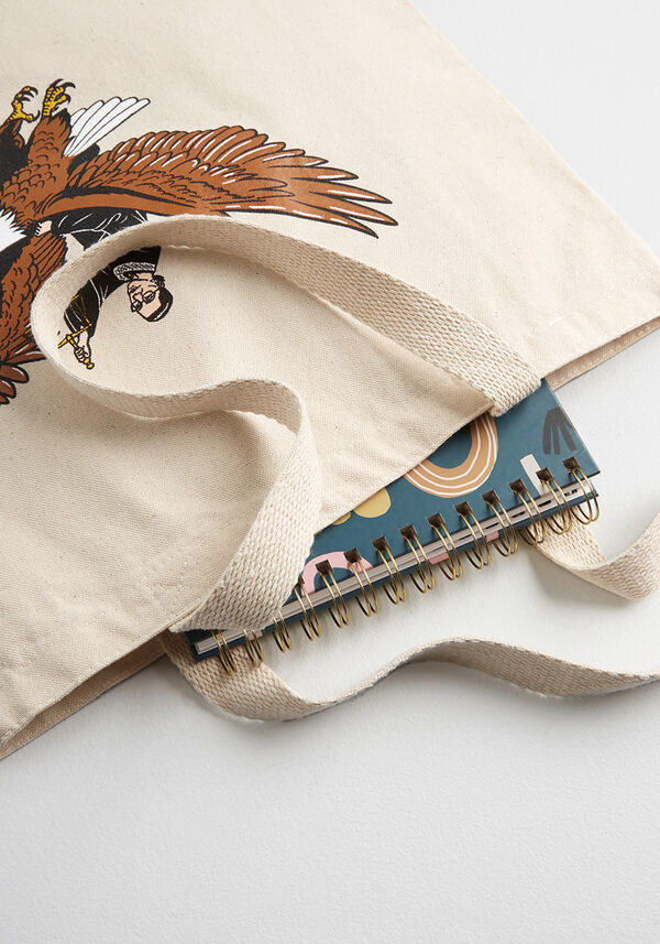 A closeup of the printed tote bag with a notebook spilling out