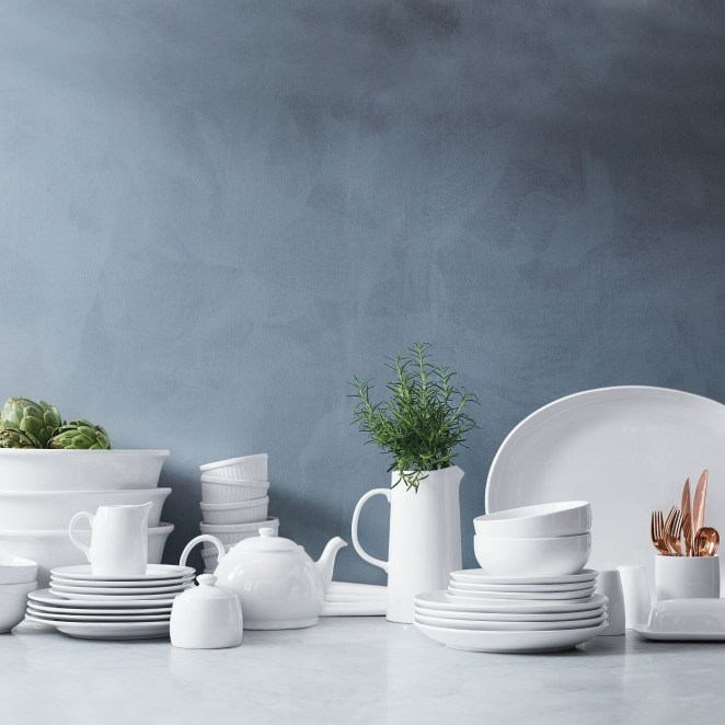 A white teapot and white table settings