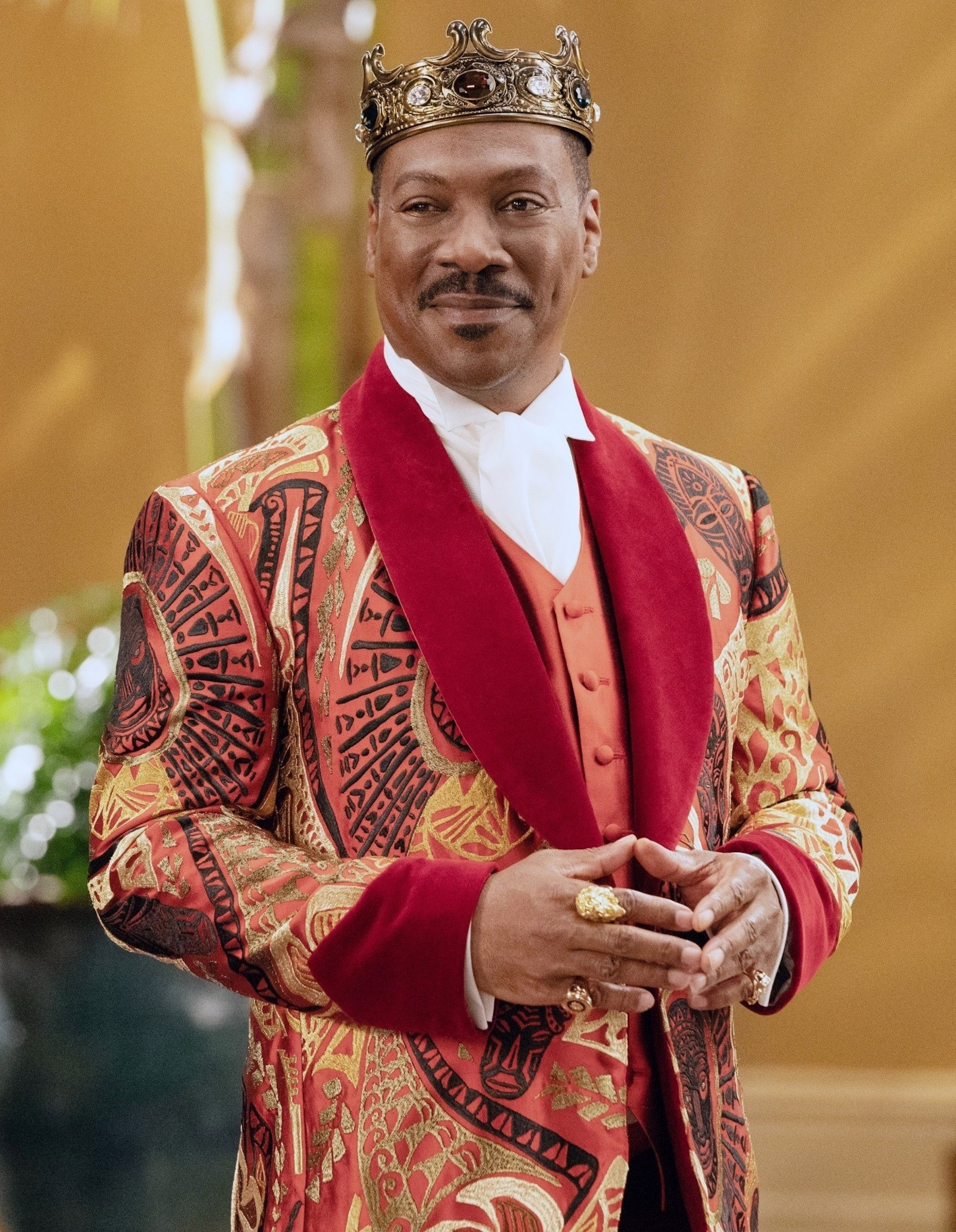 Eddie Murphy wearing a colorful blazer, a crown, and rings