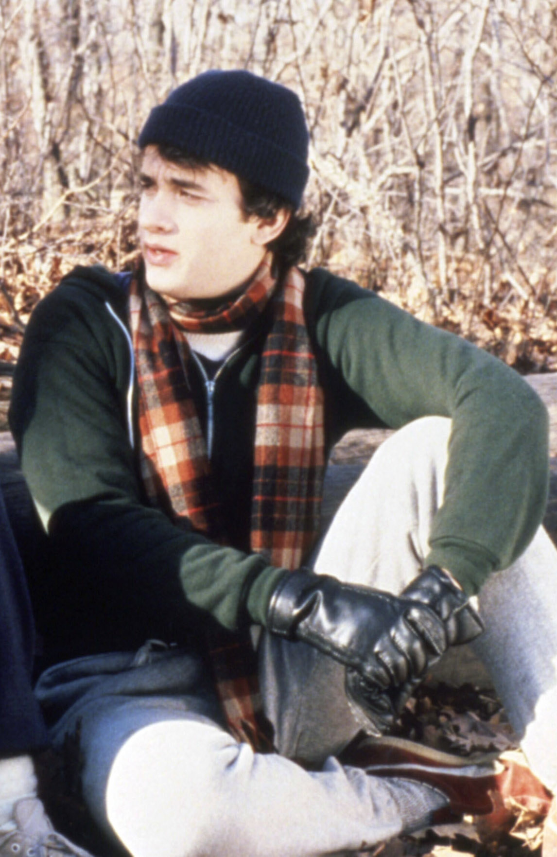 Tom Hanks kneeling down wearing sweatpants, a coat, and hat in the fall
