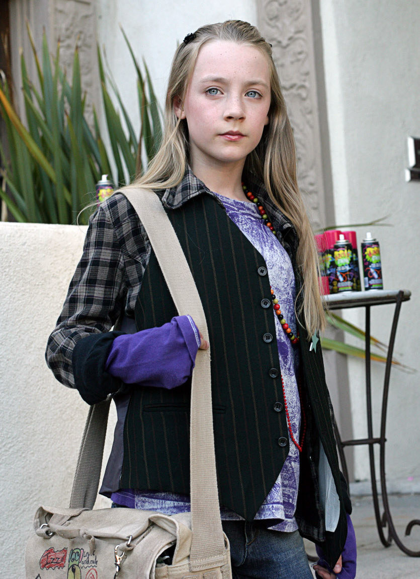 A very young Saoirse Ronan carrying a messenger backpack with long hair