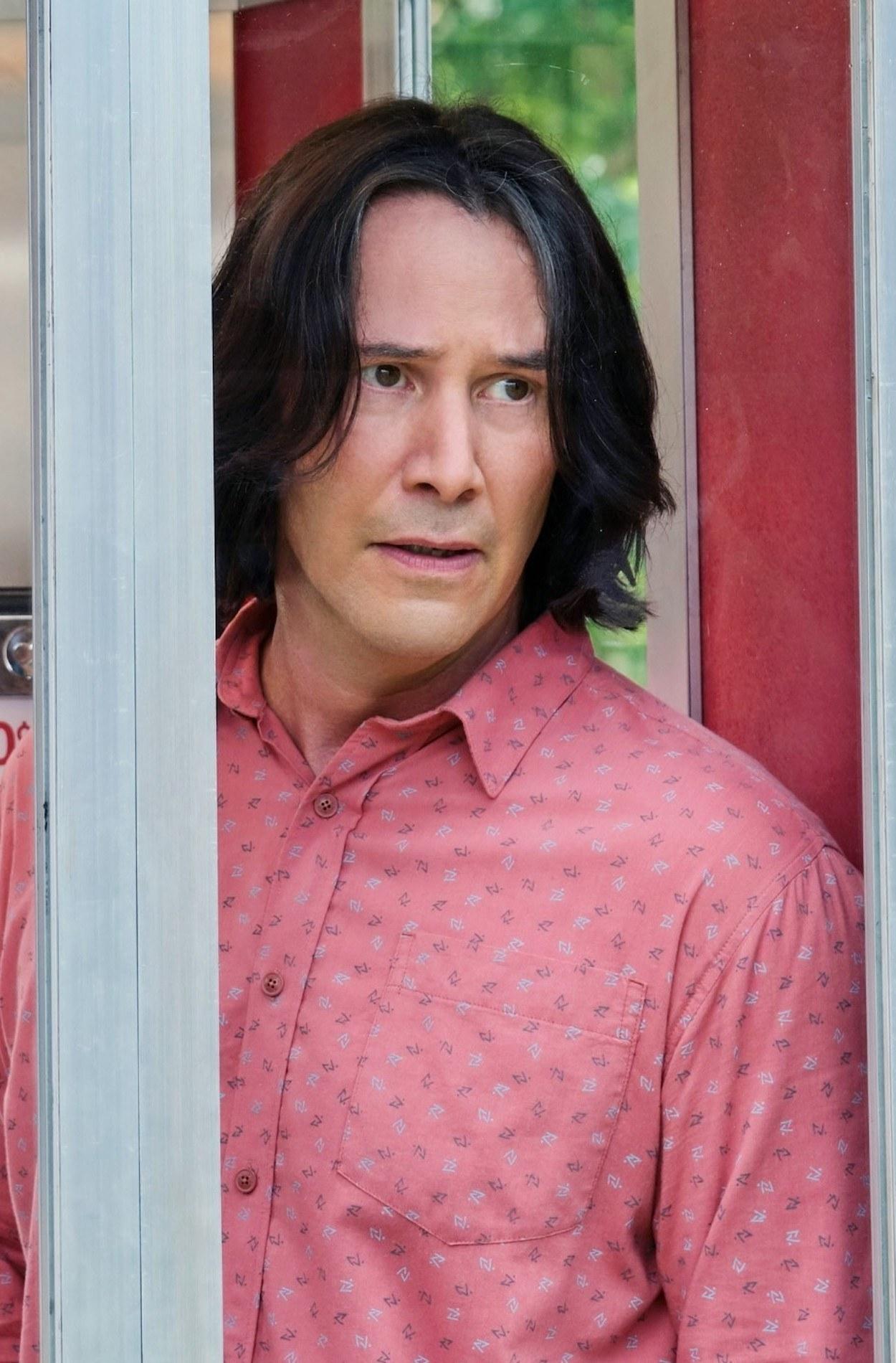 Keanu Reeves standing in a phone booth looking confused