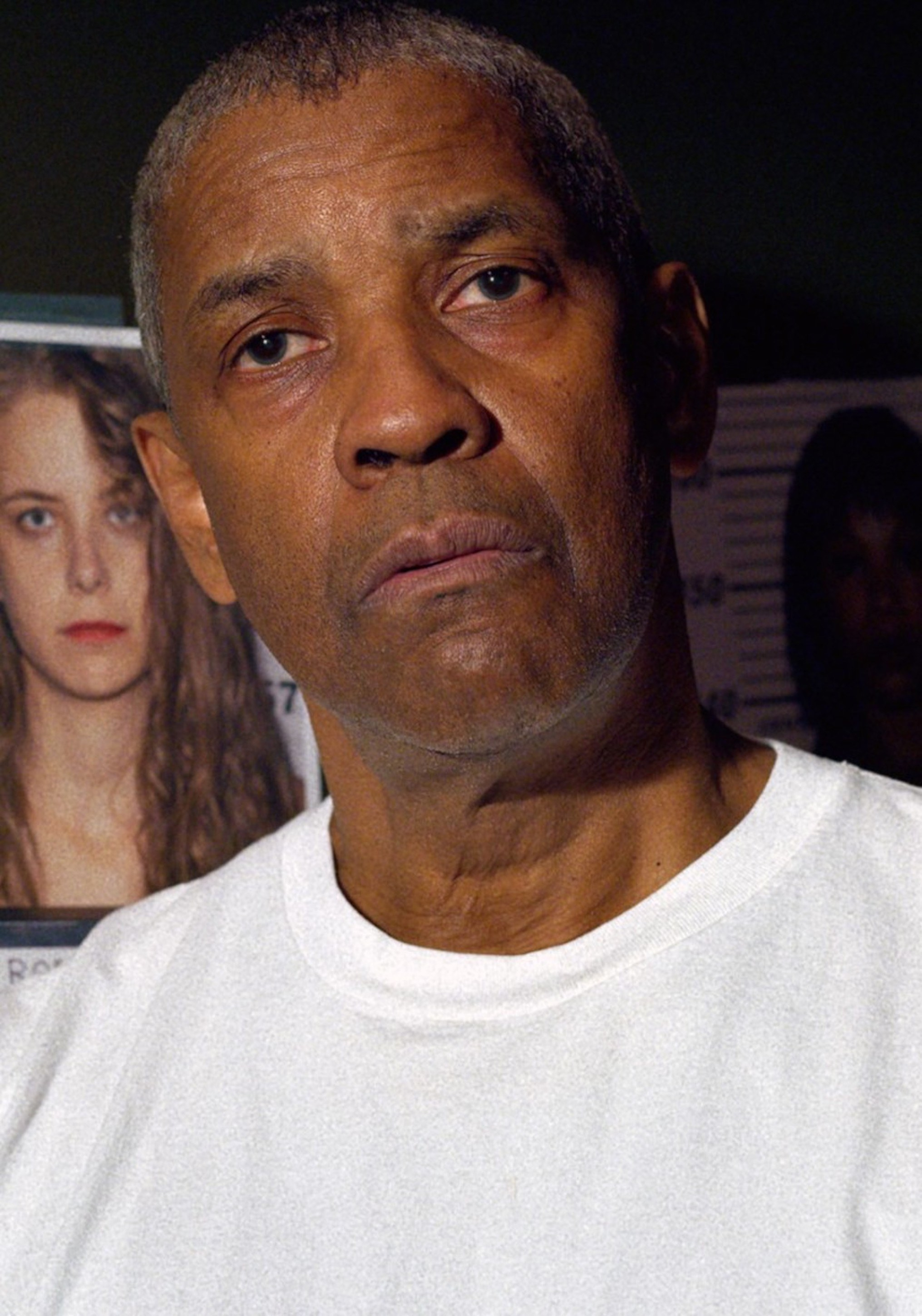 Denzel Washington wearing a white t-shirt while standing in front of images of potential suspects