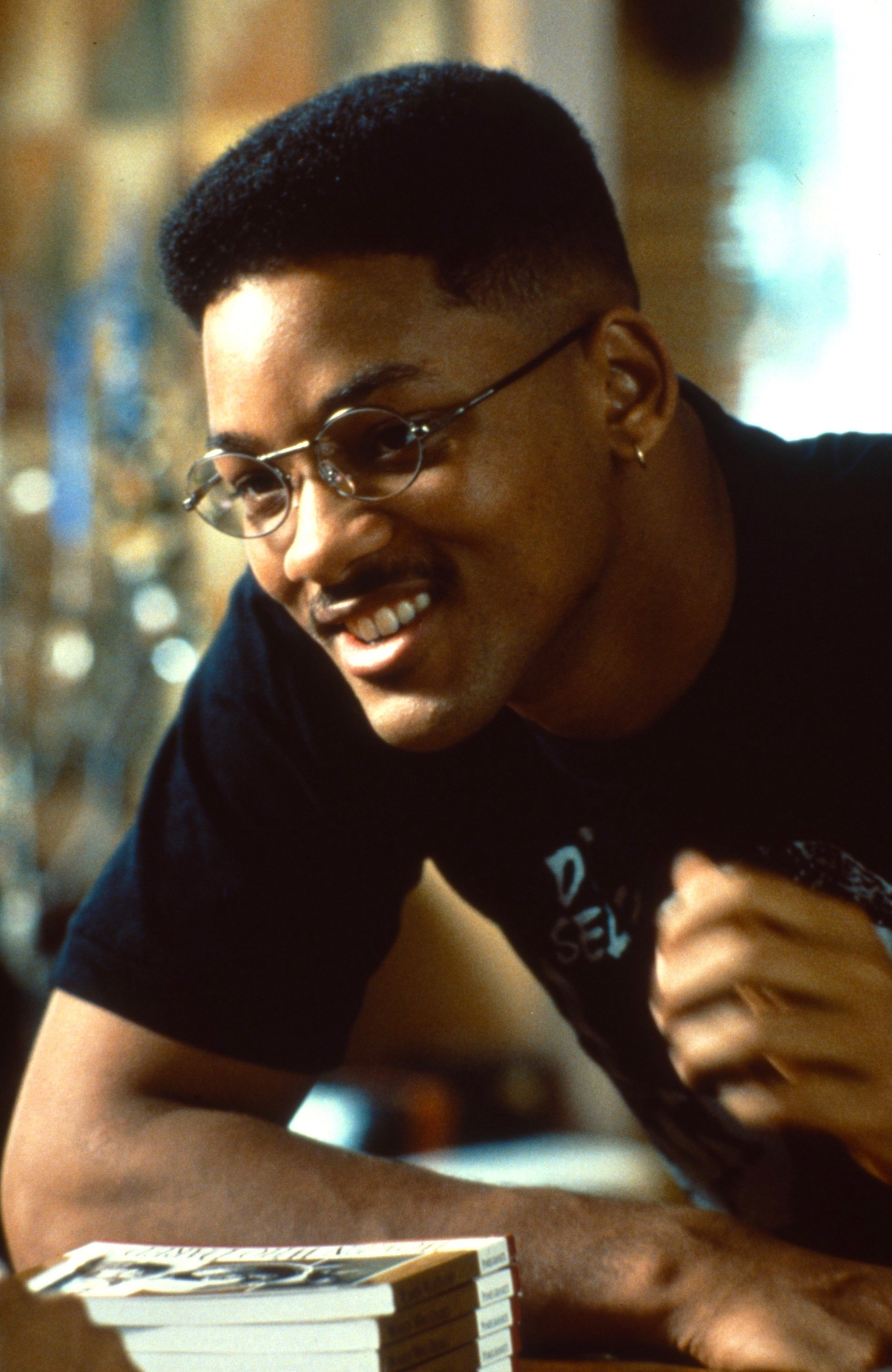 Will Smith wearing glasses, leaning on a table with a stack of books