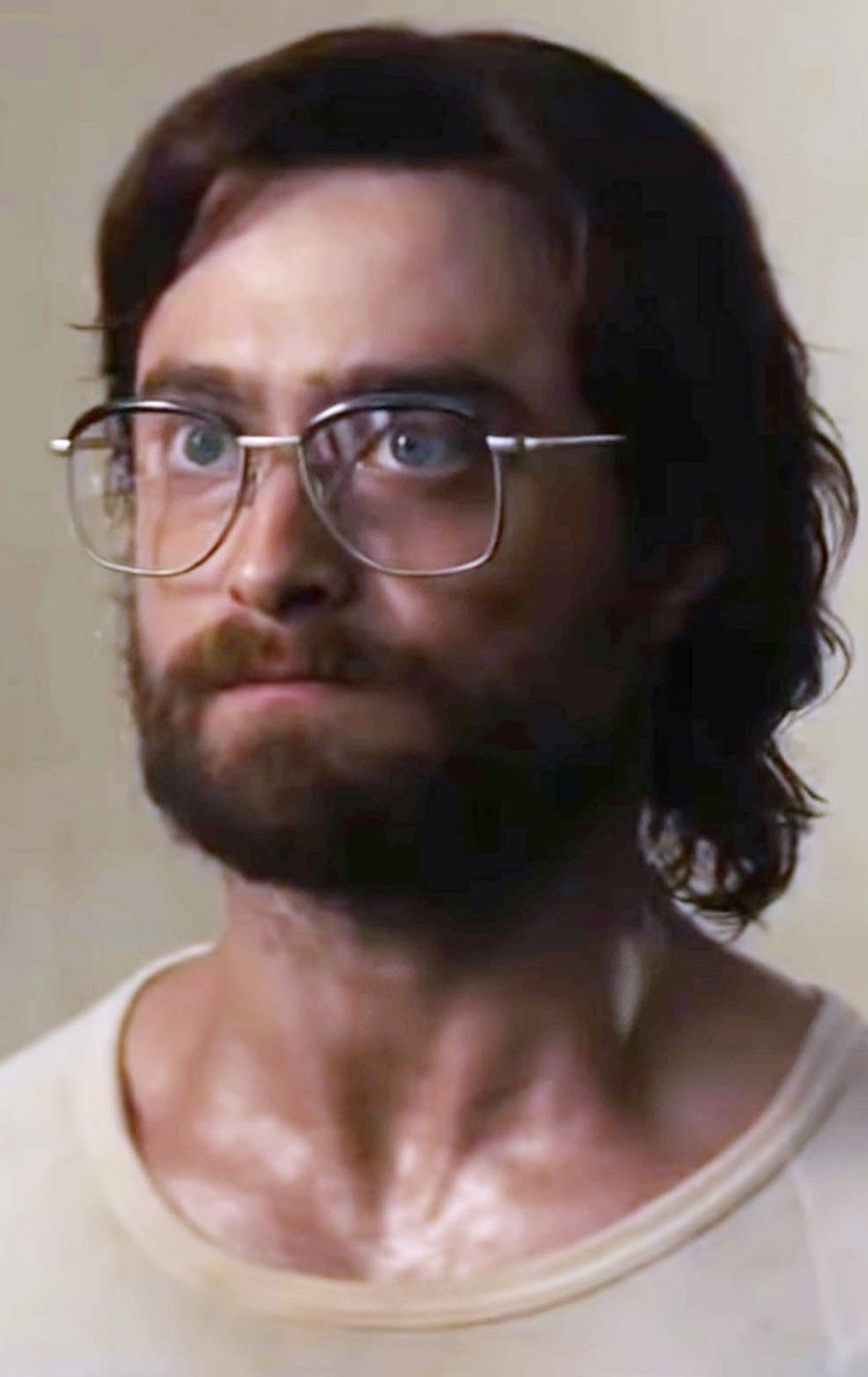 Daniel Radcliffe with long hair, a beard, oversized glasses, while sweating in a shirt