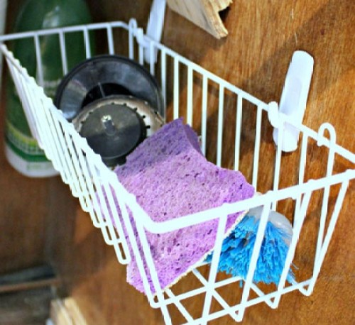 Make all that under-the-sink space work for you with the help of Command hooks and a little basket.
