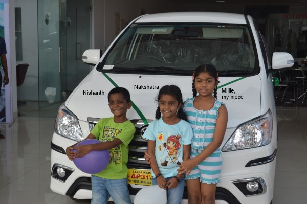 My kids and my niece infront our new car
