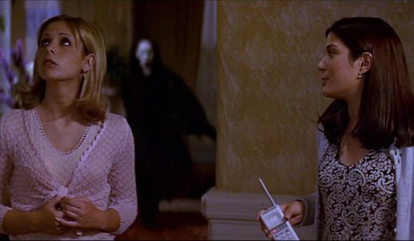 Scream 2 Ghostface sneaks up behind Sarah Michelle Gellar and her friend