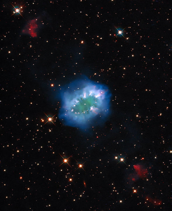 """The interaction of two doomed stars has created this spectacular ring adorned with bright clumps of gas – a diamond necklace of cosmic proportions. Fittingly known as the """"Necklace Nebula,"""" this planetary nebula is located 15,000 light-years away from Earth in the small, dim constellation of Sagitta (the Arrow)."""