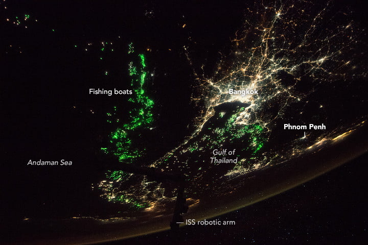 This oblique photograph, taken by an astronaut from the International Space Station, shows the city of Bangkok illuminated by city lights.