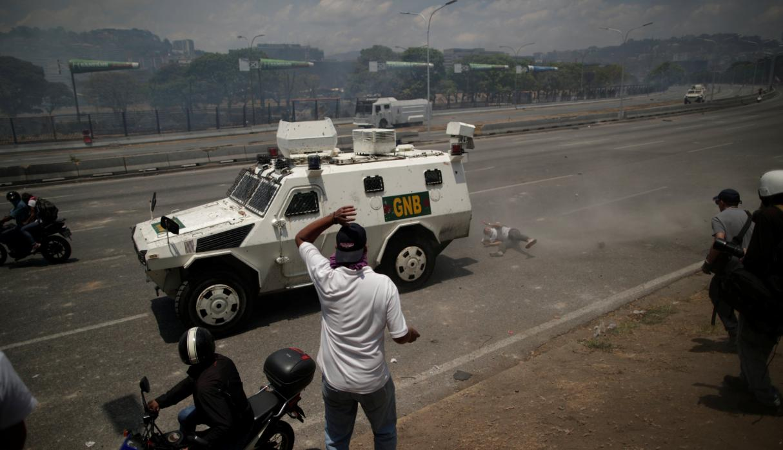 El momento en que una tanqueta militar arrolla a manifestantes en Caracas. Foto: Reuters