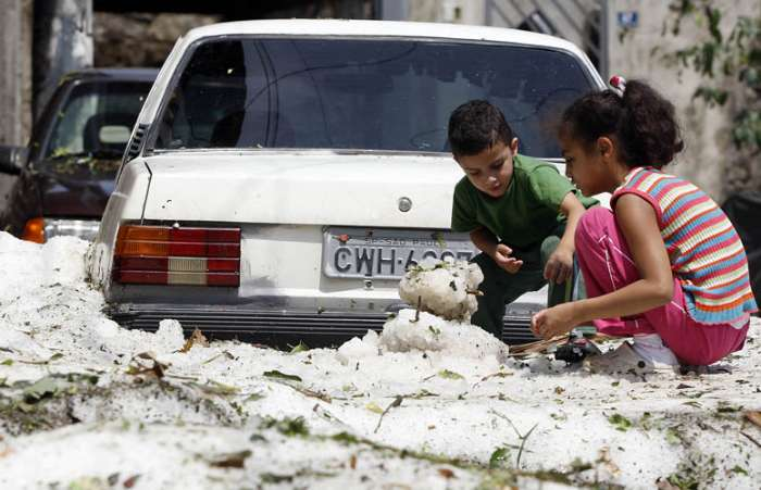 Crianças brincam com o  granizo