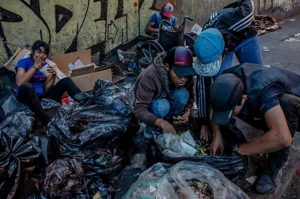 Jovens recolhem comida no lixo