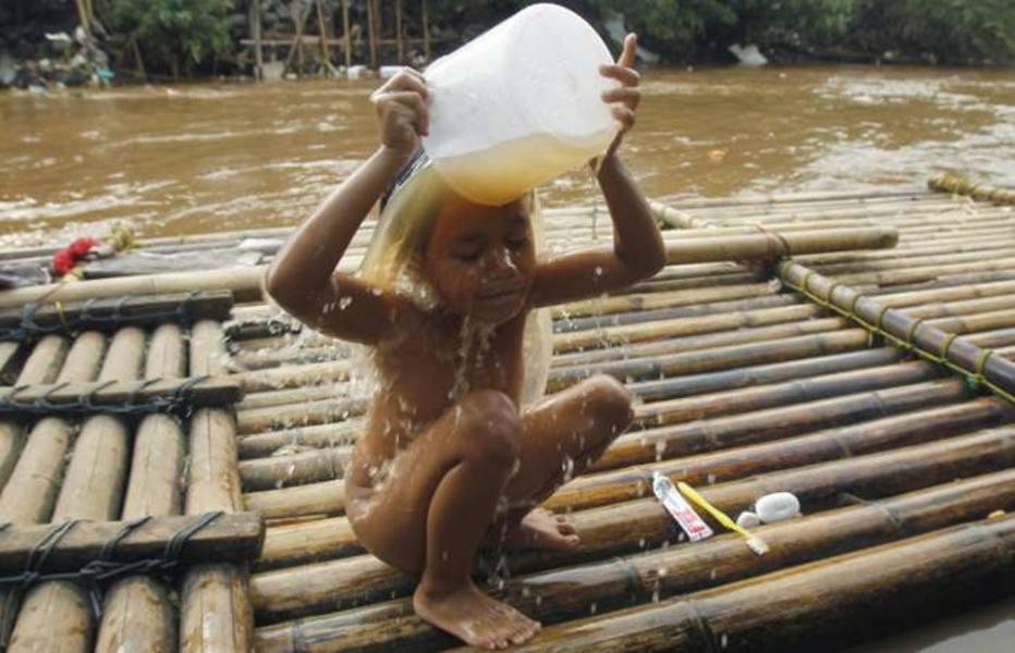 Menina se banha em rio poluído, Jakarta, na Indonésia; cidade tem mais de 9 milhões de habitantes