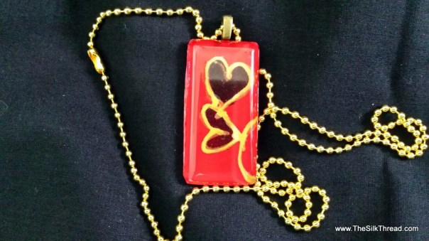 """Two gold hearts hand painted on red silk by artist. Beautiful 1"""" x 2"""" pendent necklace with 24"""" chain, free organza gift bag"""