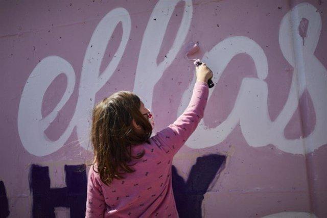 Archivo - Una niña participa en la tarea de pintar un mural.