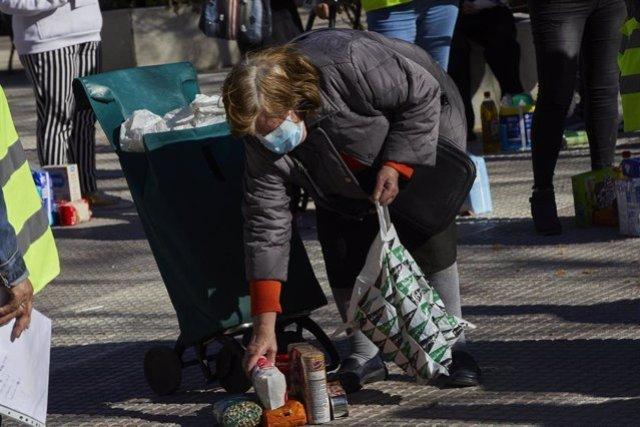 Archivo - Una mujer recoge los productos de alimentación donados por parte de la Despensa Solidaria de Chamberí.
