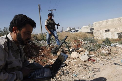 Un soldado del Ejército de Siria Libre usa un ordenador portátil mientras otro p