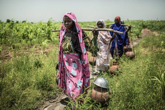 Sauda Hamid, junto a su bebe transportando cántaros de cerámica con agua