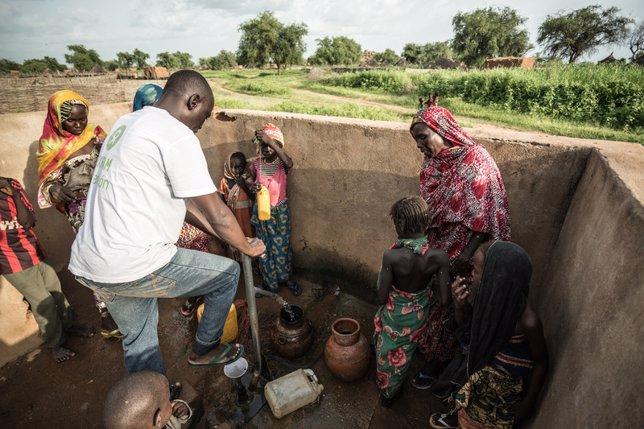 Akkoe Moussa en una fuente con más personas un hombre echa agua en un cántaro de cerámica