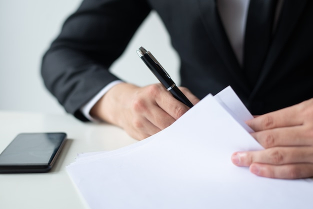 Closeup of business man signing document at office desk