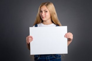 Premium Photo   Cute teenage girl with long blond hair holding white blank  poster on gray background.