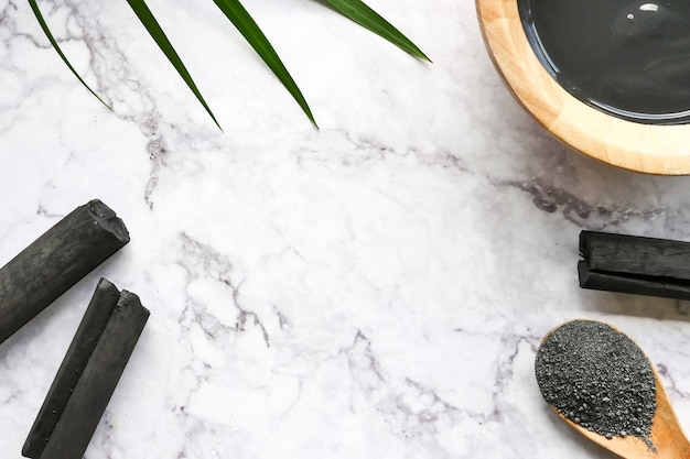 Facial mask and scrub by activated charcoal powder on marble table ...