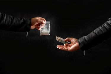 Hand of a drug addict with money buying a dose of cocaine