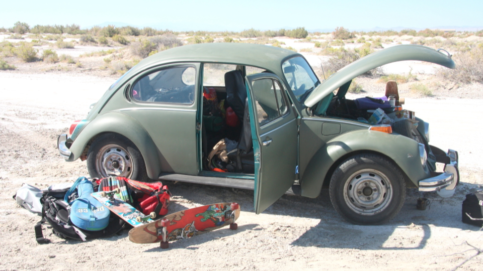 Guy Laying On Old Beetle Car