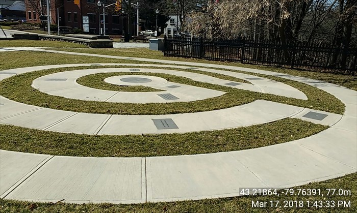 Simple four circuit round labyrinth in stone sectioned walk way with memorial plaques inscribed.