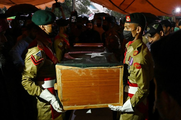 Soldiers carry the flag-drapped coffin of the late Pakistan's nuclear scientist Abdul Qadeer Khan during his funeral outside the Faisal Mosque following his death in Islamabad this week