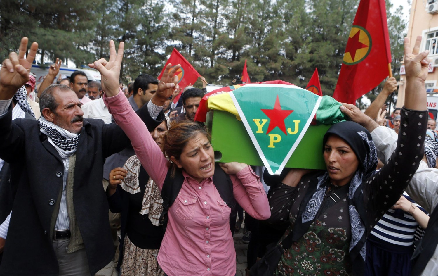 Kurds gesture and shout slogans as they carry the coffin of one of the four Kurdish women fighters killed during clashes against Islamic State fighters in Kobani, Syria, in 2014.