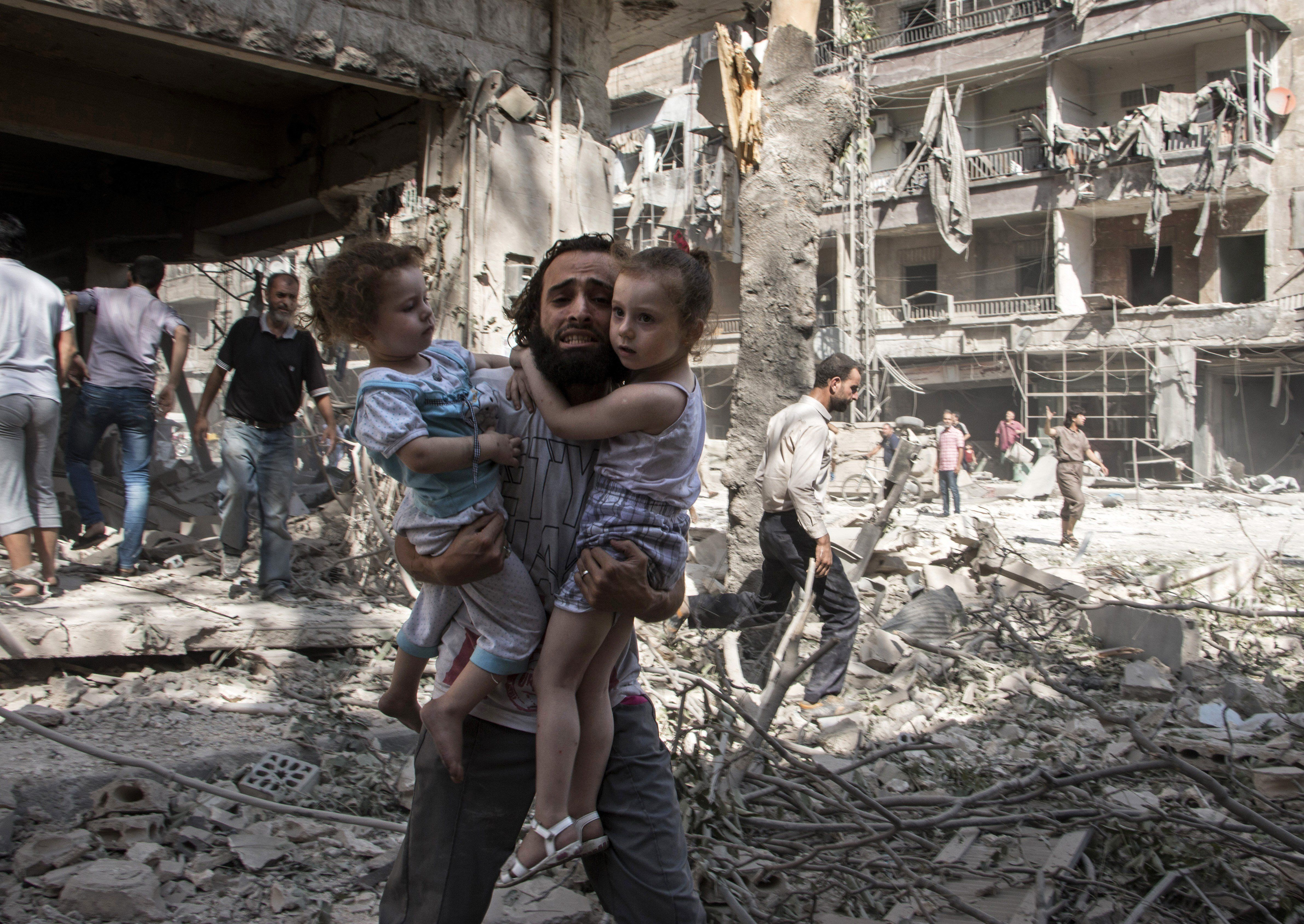 "<span class='image-component__caption' itemprop=""caption"">A Syrian man carries his two girls as he walks across the rubble following an airstrike in Aleppo on Sept. 17, 2015.</span>"