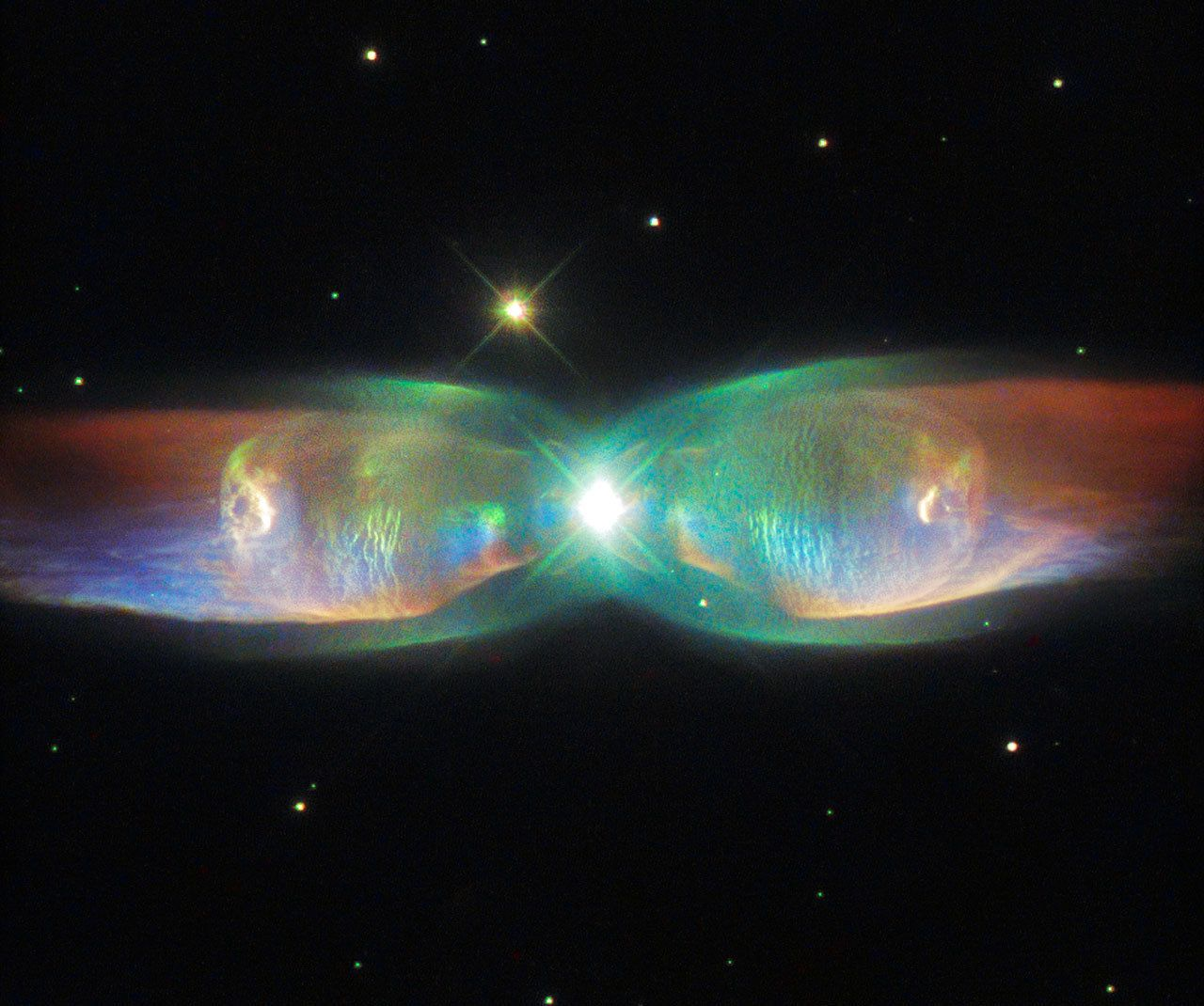 "<span class='image-component__caption' itemprop=""caption""><span style=""font-family: Arial, Helvetica, sans-serif; font-size: 14px; line-height: 20px; background-color: #eeeeee;"">The shimmering colors visible in this Hubble Space Telescope image show off the remarkable complexity of the Twin Jet Nebula, or PN M2-9.</span></span>"