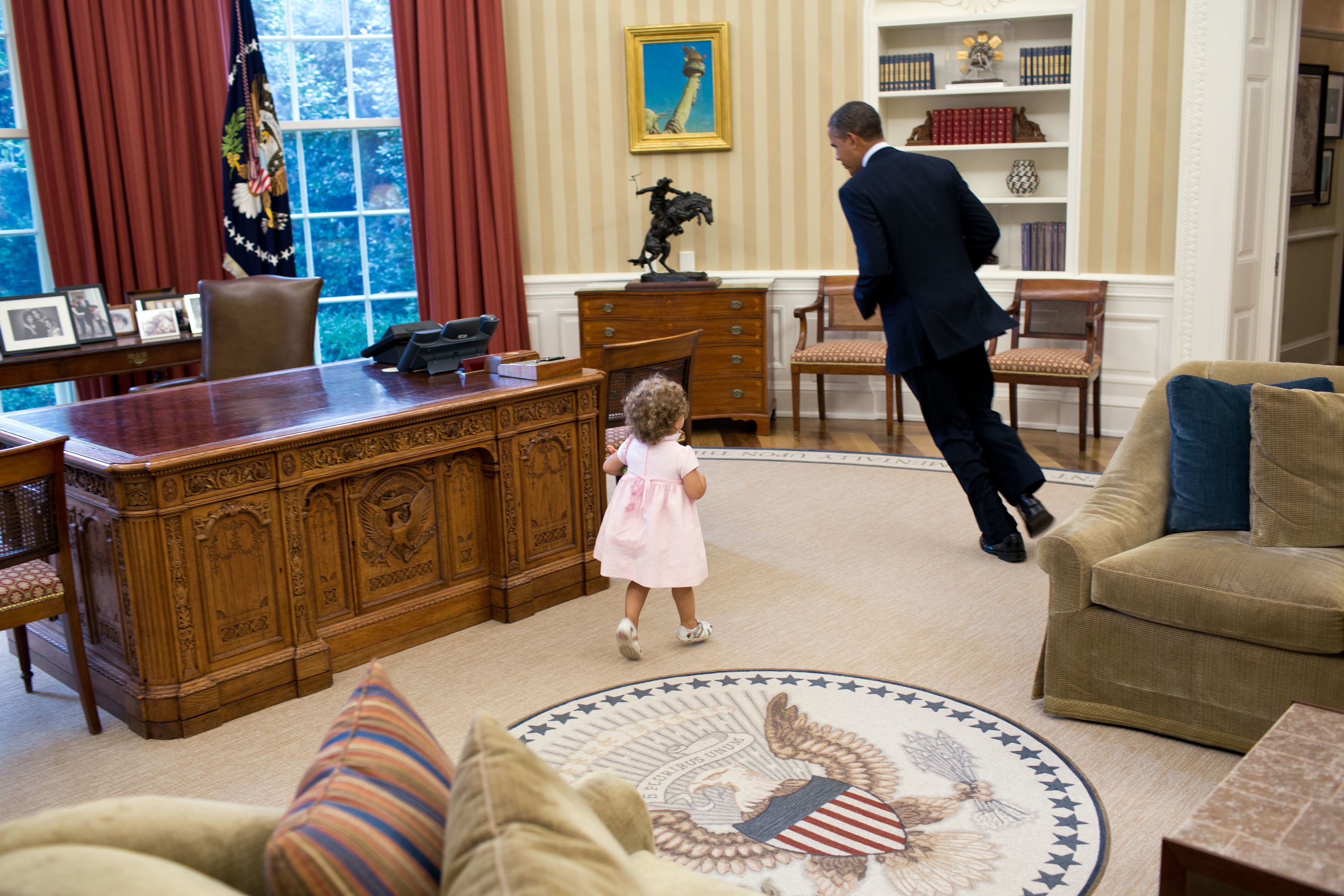 President Barack Obama runs around his desk in the Oval Office with Sarah Froman, daughter of Nancy Goodman and Mike Froman, Deputy National Security Advisor for International Economics, July 9, 2012. (Official White House Photo by Pete Souza)