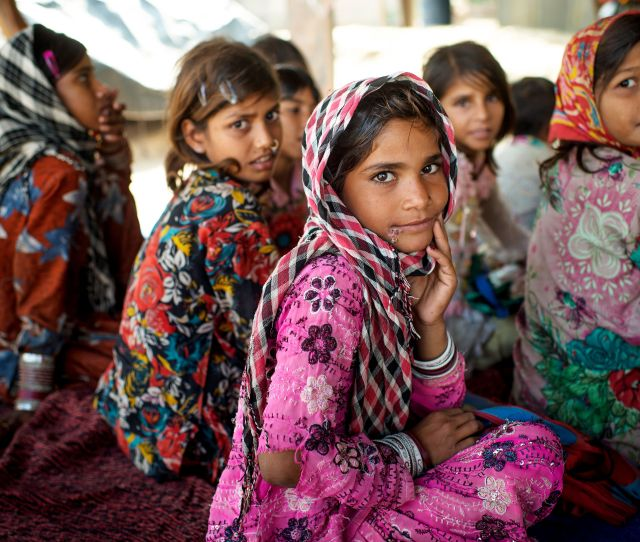 Children Sit On The Ground With A Temporary Roof To Protect Them Against The Strong Sun