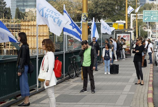 People stop and stand in silence on a street in Tel Aviv.