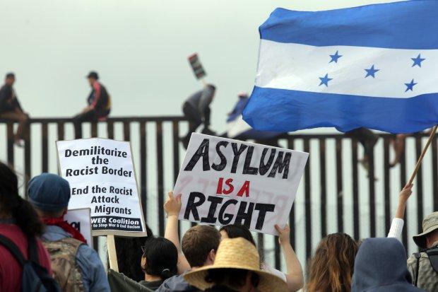 Pro-migrant caravan demonstrators, including a woman waving a Honduran flag, rallyas some people climb the border wall.