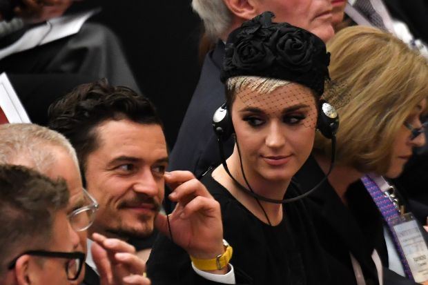 Katy Perry looks toward British actor Orlando Bloom asthey listen via headphones to a translation of Pope Francis' spee