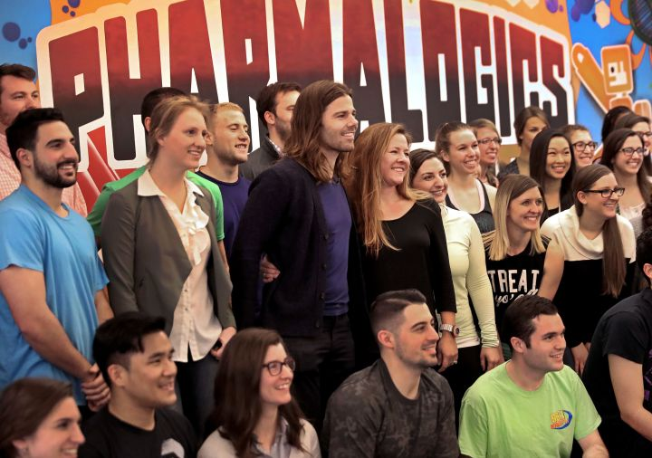 PharmaLogics employees pose with their CEO Megan Driscoll (center right) and Dan Price (center left),who influenced Meg