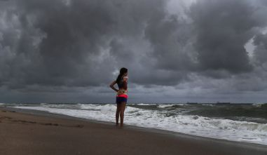 Alicia Herrera, 10, visiting from Germany, doesn't let dark clouds ruin her day at the beach in Fort Lauderdale, Florida, on