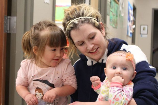 Amanda Williammee snuggles 2-year-old Taycee and 6-month-old Jayde after picking them up at Horizons. The program's day care