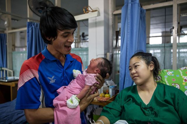 Arif Somsingjai, 30, a construction worker, holds his 2-day-old baby boy Karis, his second child, as his wife Chayanid T