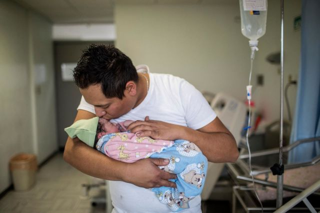 Yair Cruz, 26, holds his newborn baby girl and third child, Mia Gisele, at the Instituto Nacional de Perinatologí