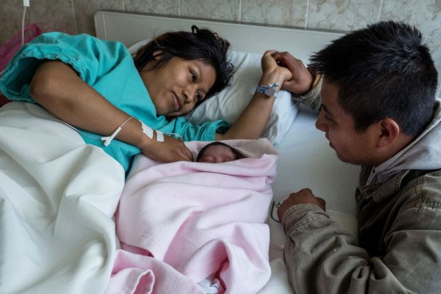 Eli Rodriguez Zempahua, 22, looks at his wife Lucia and newborn baby girl Mage Rodriguez Trinidad at the Zongolica IMSS